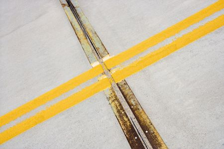 yellow line: Detail of solid double yellow line in road  crossing metal strips in cement. Stock Photo