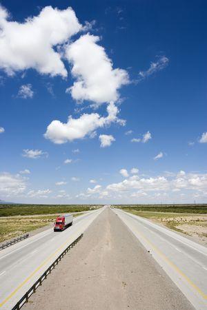 ハイアングルビュー: トラクター トレーラー トラックと青曇り空で高速道路の高角度のビュー。