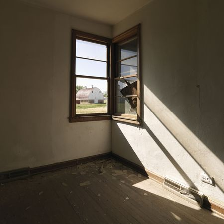 Dark empty abandoned room with sunrays stretching across wall from corner window. Stock Photo - 1832285