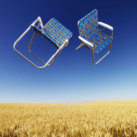 Two lawn chairs in mid-air above a field of wheat with blue sky. photo