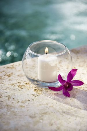 purple orchid: Lit candle in glass bowl with purple orchid next to pool.
