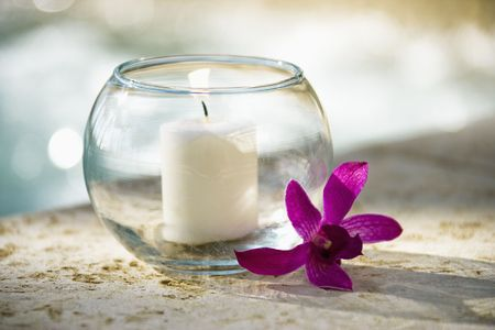 Lit candle in glass bowl and purple orchid beside pool. Stock Photo - 1841704