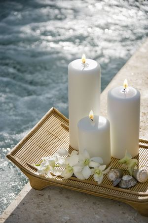 beside: Lit pillar candles on tray with white orchids beside pool. Stock Photo