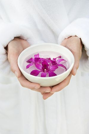 Caucasian womans hands holding bowl with purple orchids floating in water. photo