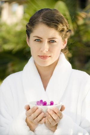 Attractive Caucasian mid-adult woman in white robe holding bowl of purple orchids floating in water. Stock Photo - 1841843