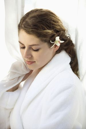 Pretty Caucasian mid-adult woman wearing white terry robe with white orchid flower in hair. Stock Photo - 1841847