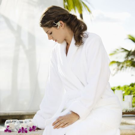 Attractive Caucasian mid-adult woman at spa wearing white robe sitting looking down at candles and orchids. Stock Photo - 1841758