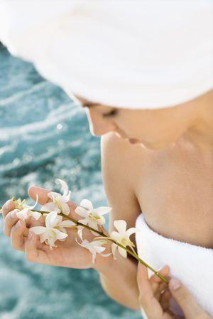 Pretty Caucasian mid-adult woman wearing towel on head holding flowers beside pool. Stock Photo - 1841780