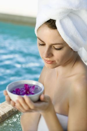 Caucasian mid-adult woman wearing white terry robe holding bowl of purple orchids next to pool. Stock Photo - 1841788