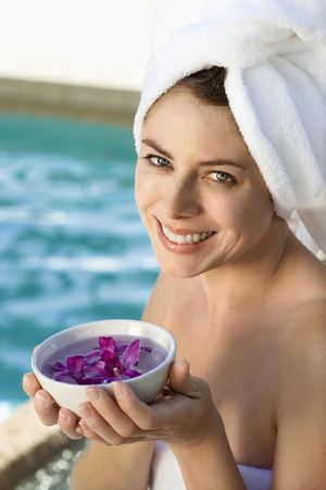 Caucasian mid-adult woman wearing towel around head and body holding bowl of purple orchids next to pool. Stock Photo - 1841889