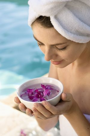 Caucasian mid-adult woman wearing towel around head and body holding bowl of purple orchids next to pool. Stock Photo - 1841842