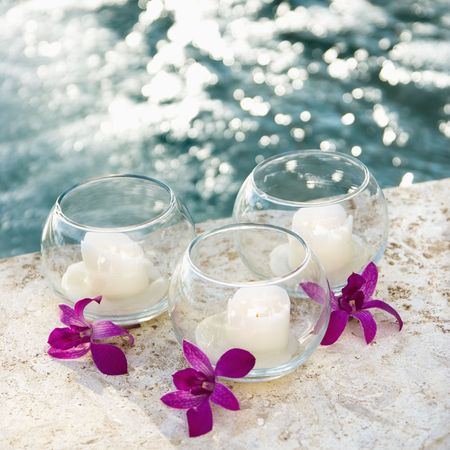 Three candles and three purple orchids by pool. Stock Photo - 1841227
