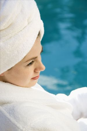 Caucasian mid-adult woman wearing robe and towel on head sitting next to pool. Stock Photo - 1841832