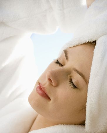 Caucasian mid-adult woman wearing towel on head with eyes closed relaxing. photo
