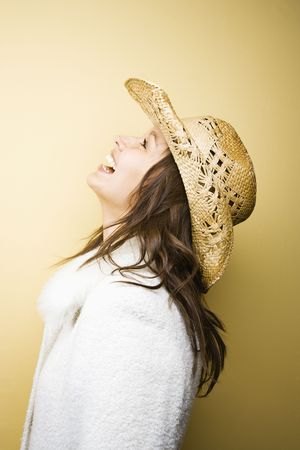half length posed: Profile of young adult Caucasian woman wearing cowboy hat leaning backwards laughing. Stock Photo