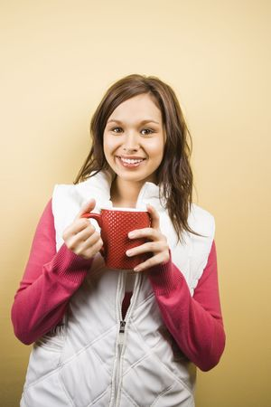 half length posed: Young adult Caucasian woman holding coffee cup and smiling at viewer.