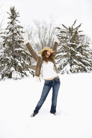 arms above head: Carefree Caucasian young adult female standing with arms above head in snow wearing straw cowboy hat. Stock Photo