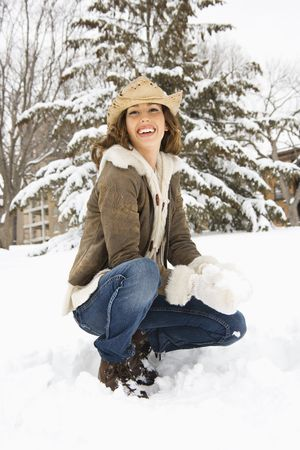 Caucasian young adult female smiling at viewer while kneeling in snow with snowball and wearing straw cowboy hat. Stock Photo - 1841967