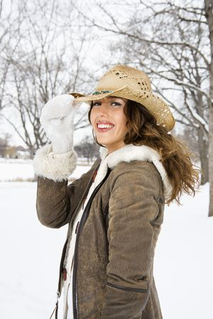 tilting: Caucasian young adult female smiling and tilting straw cowboy hat at viewer.