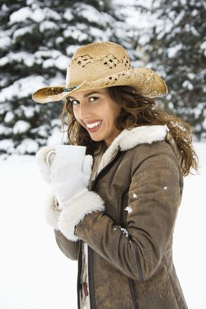 Caucasian young adult female wearing straw cowboy hat outdoors in snow holding coffee cup and smililng at viewer. Stock Photo - 1841987