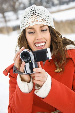 half length posed: Smiling Caucasian young adult female in winter clothing pointing video camera at viewer.