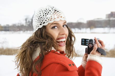 Smiling Caucasian young adult female in winter clothing holding video camera and looking over shoulder at viewer. Stock Photo - 1841892