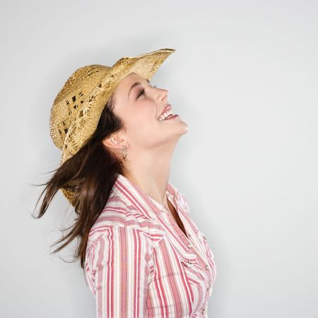 Profile of young Caucasian woman wearing cowboy hat smiling with wind blowing hair. photo