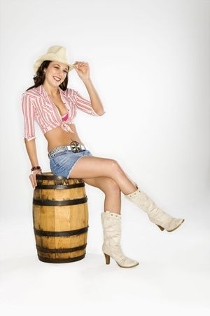 tilting: Young Caucasian woman dressed as cowgirl sitting on a barrel and tilting hat at viewer. Stock Photo