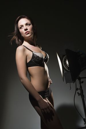 Sexy Caucasian woman in lingerie standing next to spotlight. photo