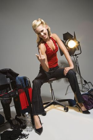 Pretty young Caucasian blonde woman sitting with studio lights giving middle finger. photo