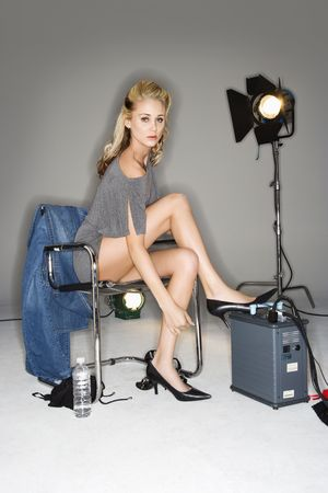 Pretty young Caucasian blonde woman sitting with studio lights. photo