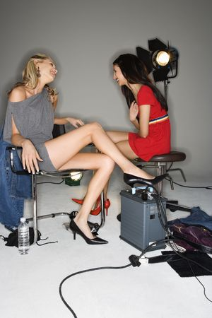 Pretty young women sitting with studio lights talking and laughing. photo