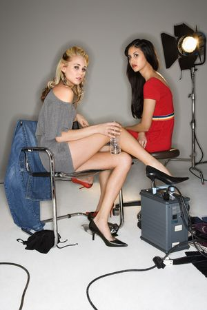 behind the scenes: Pretty young women sitting with studio lights.