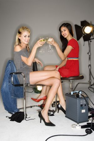 Pretty young women sitting with studio lights toasting wine and smiling. photo