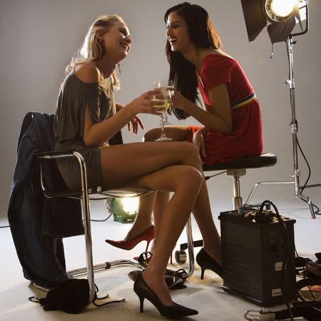 behind the scenes: Pretty young women sitting with studio lights drinking wine and smiling.