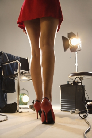 Low angle of young sexy womans legs with photography studio equipment.