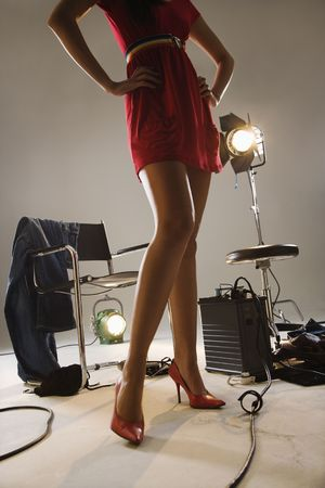 behind the scenes: Low angle of young sexy woman with photography studio equipment. Stock Photo