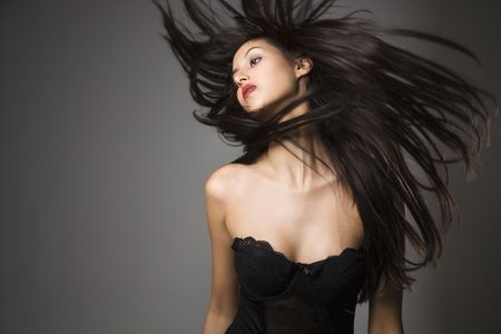 Portrait of pretty young woman flinging long black hair into air. Stock Photo - 1841831