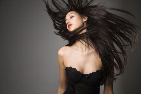 black hair: Portrait of pretty young woman flinging long black hair into air.