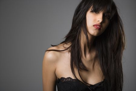 Head and shoulder portrait of pretty young woman with long black hair. photo
