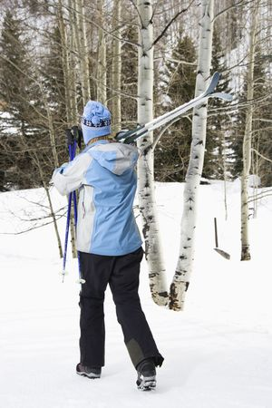 ski walking: Rear view of mid adult Caucasian female skier wearing blue ski clothing walking and carrying skis on shoulder.