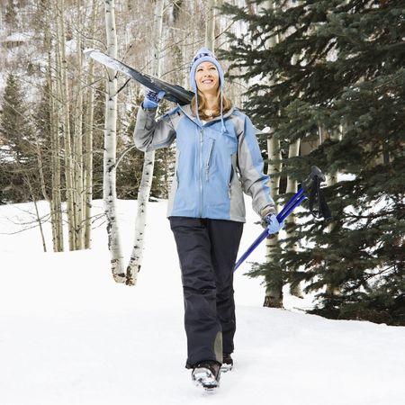 ski walking: Mid adult Caucasian female skier wearing blue ski clothing walking and carrying skis on shoulder.