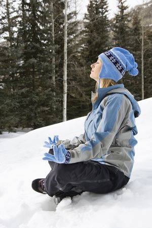 winter woman: Side view of mid adult Caucasian woman wearing blue ski clothing sitting in snow in lotus position.