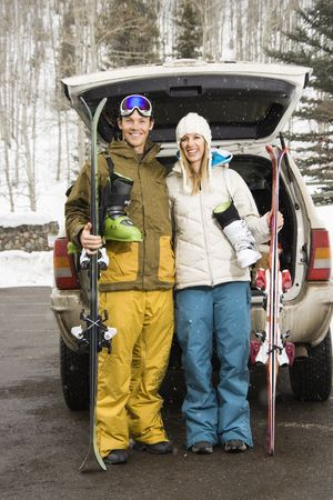 Young couple wearing winter clothes standing by automobile with ski equipment smiling. photo