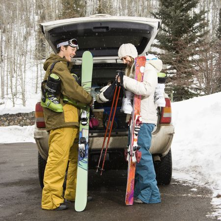 unloading: Young couple wearing winter clothes unloading ski equipment from vehicle smiling and laughing.