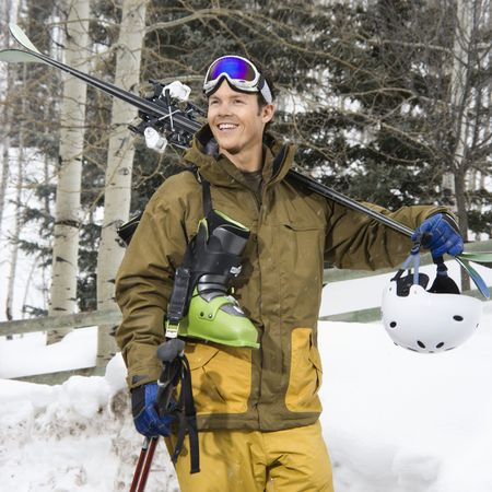 ski walking: Attractive man in winter clothing walking in snow carrying ski equipment and smiling.