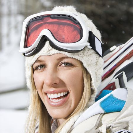 Attractive young blond woman in winter ski gear smiling. photo