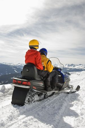 Man and woman riding on snowmobile in snowy mountainous terrain. photo