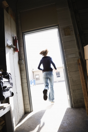 escape: Woman running through open door from building to sunny outside. Stock Photo