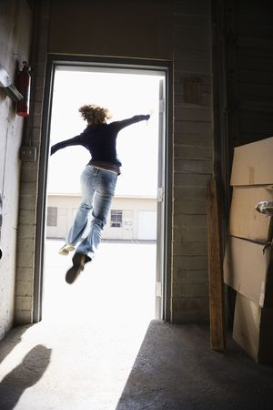 out door: Woman running and jumping through open door from building to sunny outside.